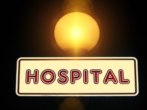 A sign for a hospital under a glowing streetlight