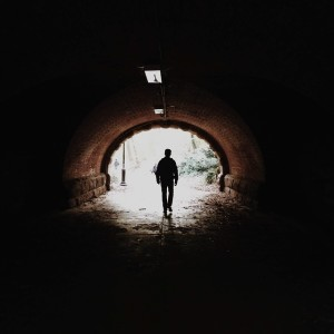 A man walking in a dark tunnel with a light at the end