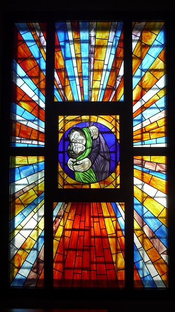 A stained glass window image of two people embracing.
