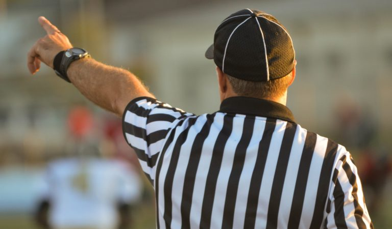 a referee in a striped shirt makes a call