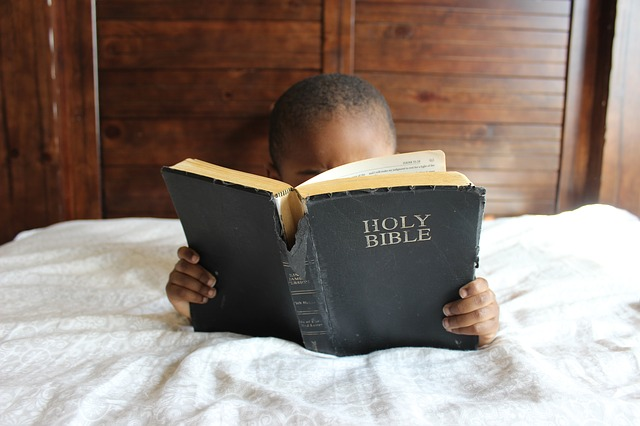 a young boy on his bed reading his Bible