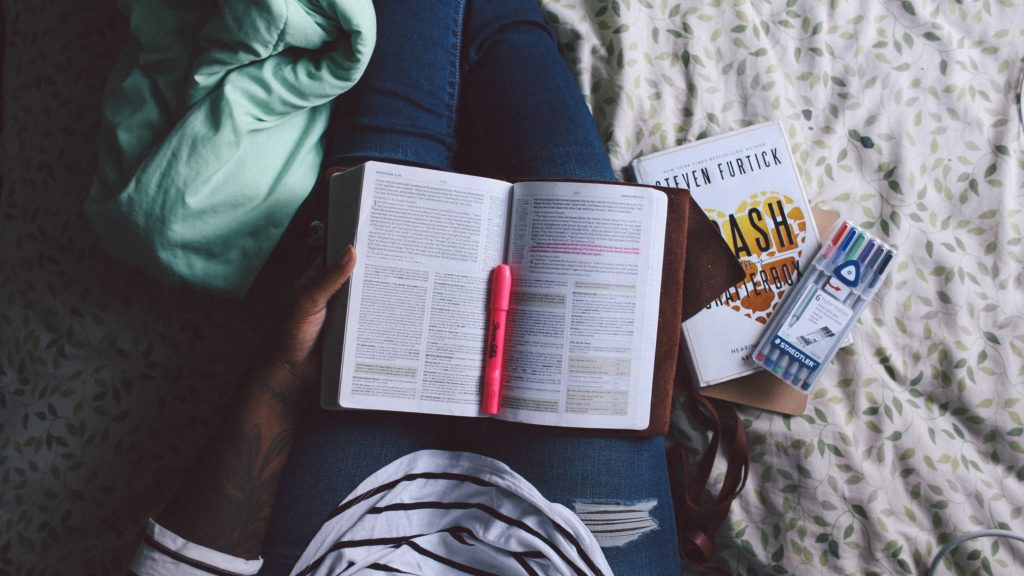 A woman sits on her bed with her Bible open on her lap, and a pink highlighter.