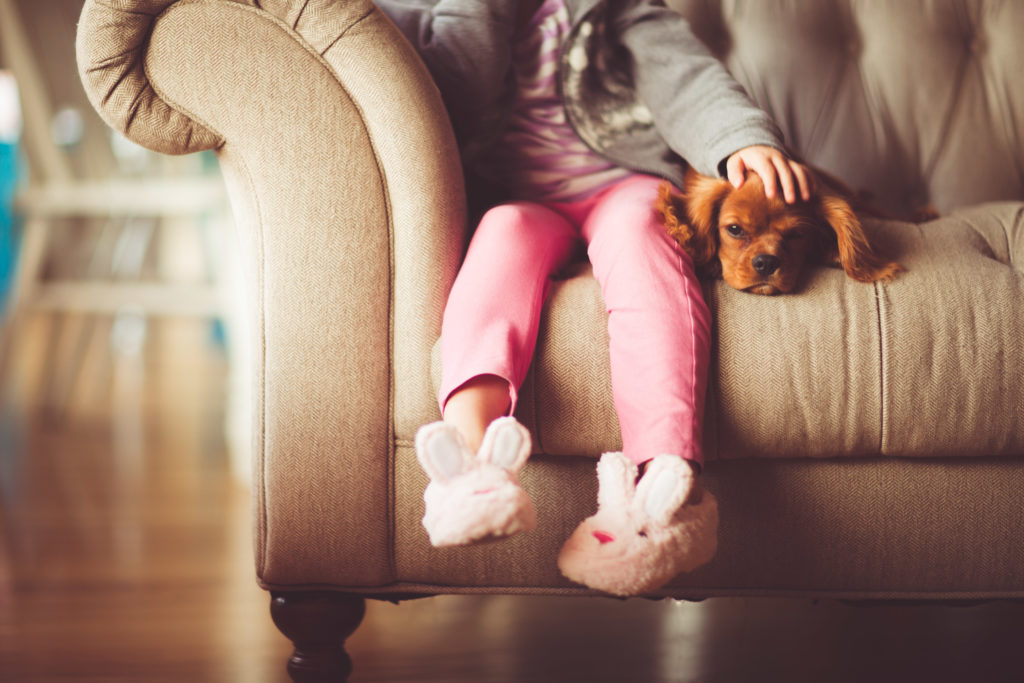 a little girl wearing bunny slippers pets a puppy