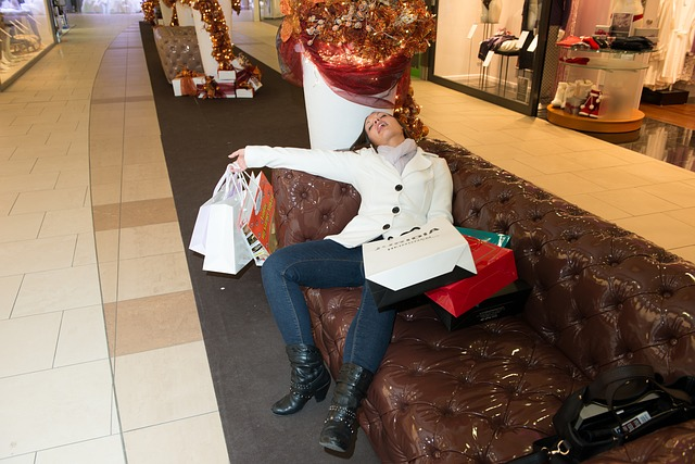 a woman reclines on a couch surrounded by shopping bags