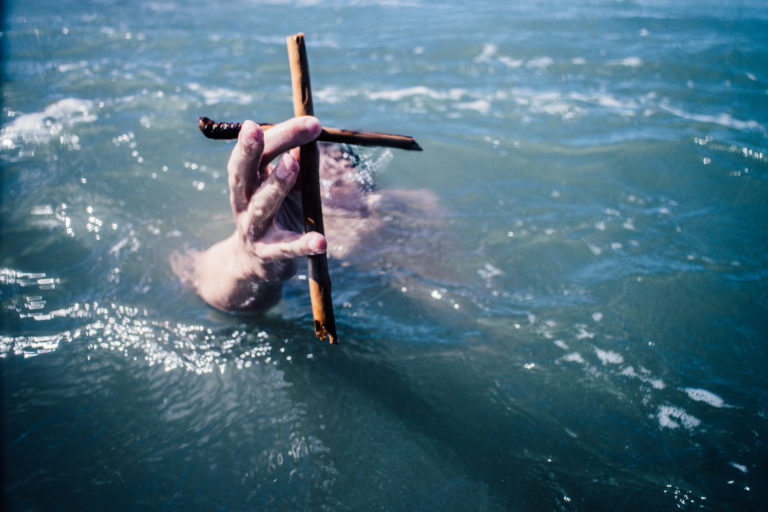 a hand clutching a cross rises out of the water