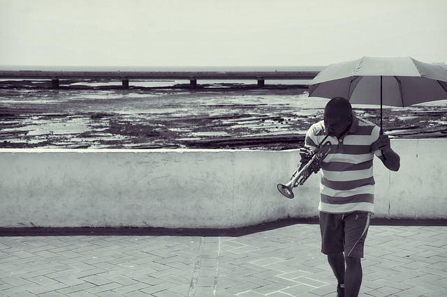 a man is holding an umbrella over his head while he plays the trumpet