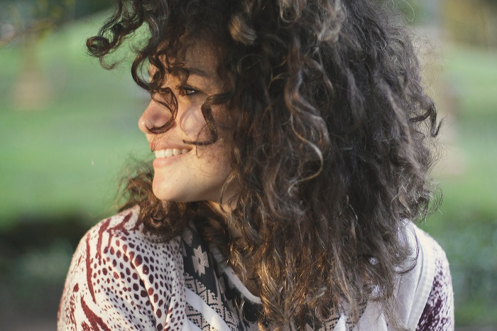 a woman with curly hair smiles