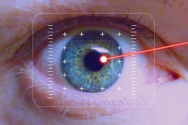 a laser beam points at the pupil of a blue eye