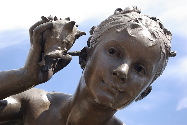 The image is of a sculpture of a girl who is holding a shell up to her ear, listening for the ocean.