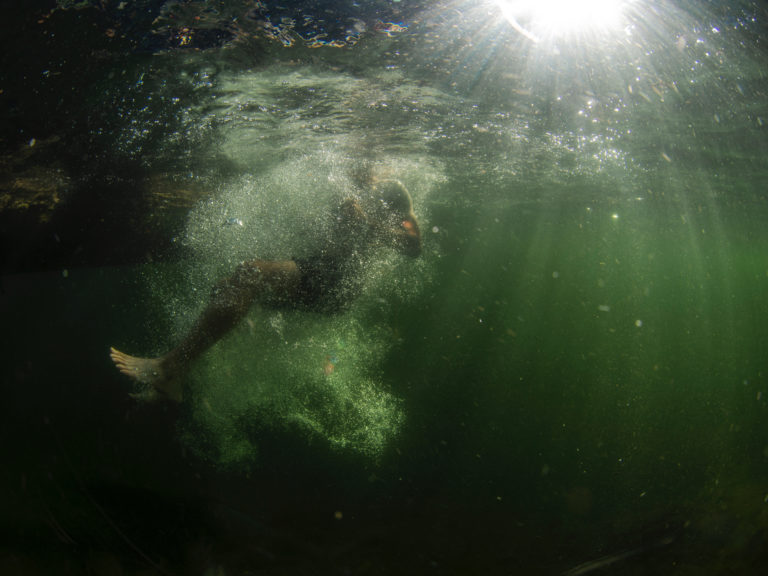 The image shows a man plunging underwater, almost hidden by bubbles.