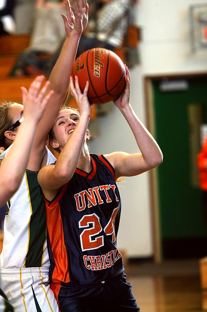 An image of a female basketball player in a crowd of opponents, about to take a shot.