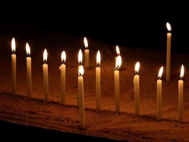 An image of 11 lit candles stuck in the sand.