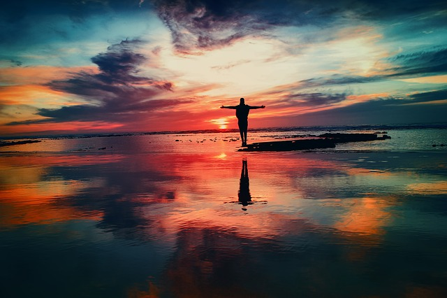 An image of a person standing on a sandbar over a calm lake, with the colors of the sunset reflected in the water.