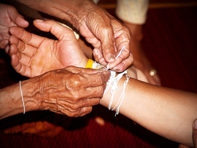 the image shows in older woman's hands tying a string around a young person's wrist