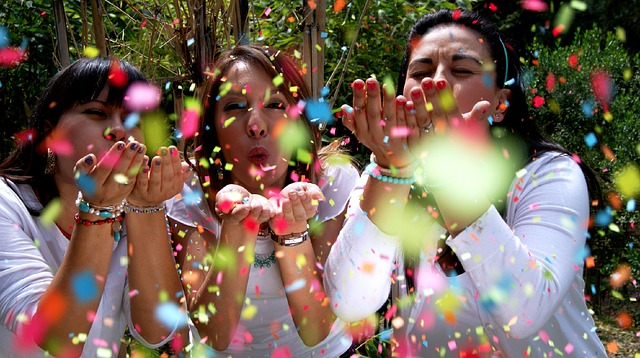women joyfully blow confetti towards the camera