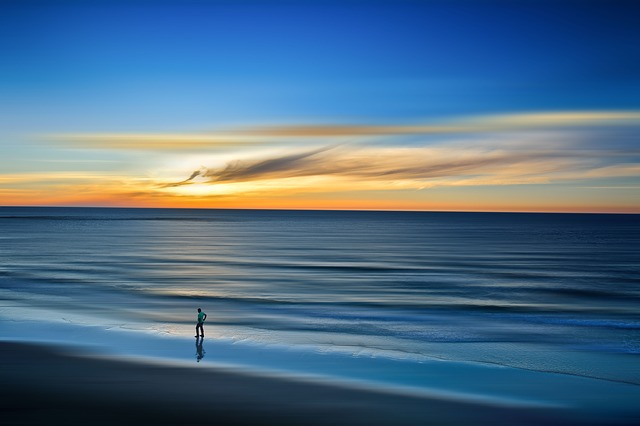 an image of a lone figure walking along a peaceful beach