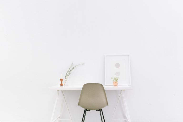 An image of a white desk in a white room, very simple and calm.