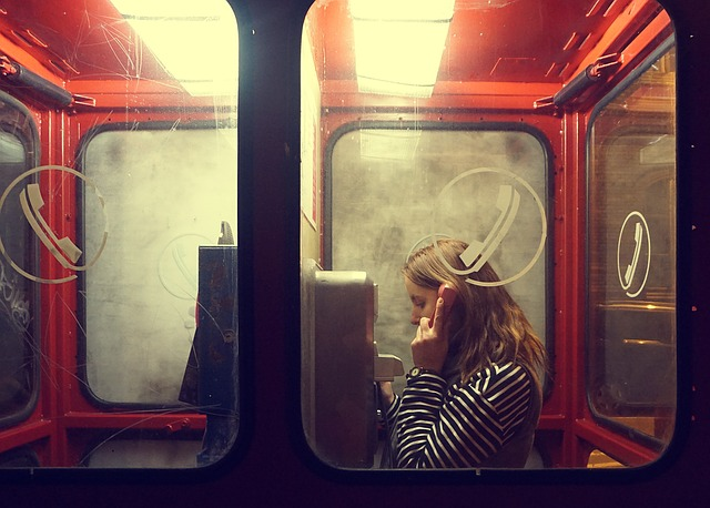 An image of a woman on the phone in a phone booth
