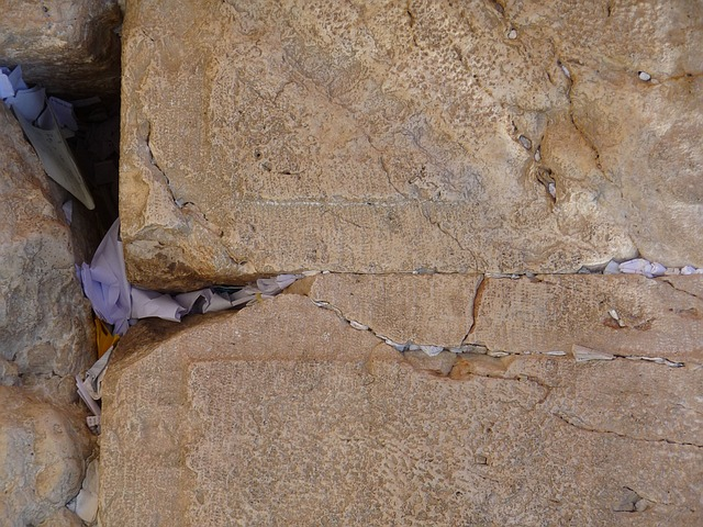 An image of paper prayers shoved in the cracks of the Wailing Wall in Jerusalem