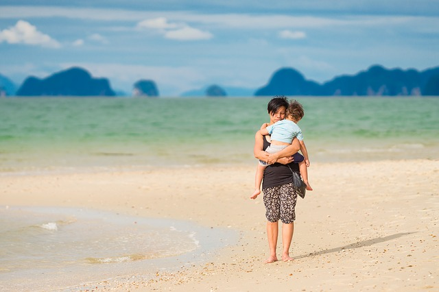 An image on a mom on a beach, with mountains across the body of water, holding her young son.