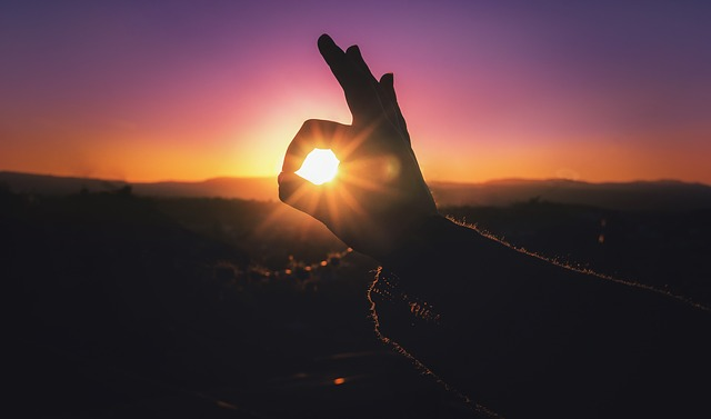 In the image, a person forms a circle around the setting sun with their index finger and thumb, focusing the shining light.