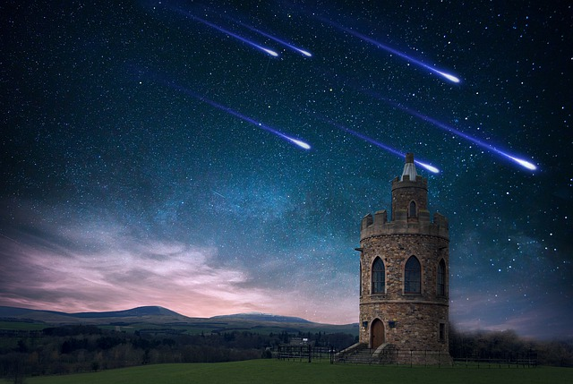 An image of a stone tower at night, with multiple shooting stars looking like they're heading for it.
