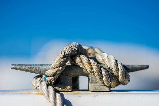 A close-up of a large rope wound around a cleat on a boat.