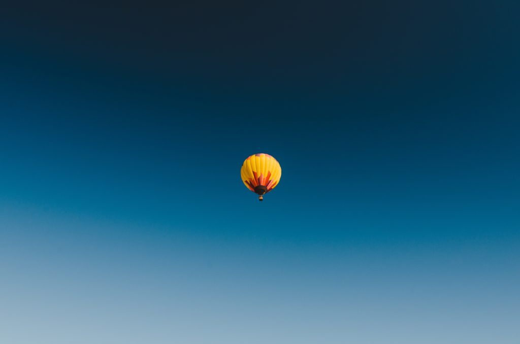 An image of a hot air balloon way off in the distance of a deep blue sky.
