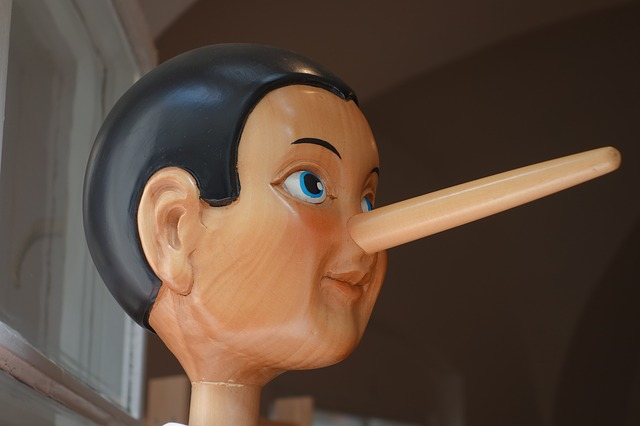 An image of a wooden Pinocchio doll with a long nose.