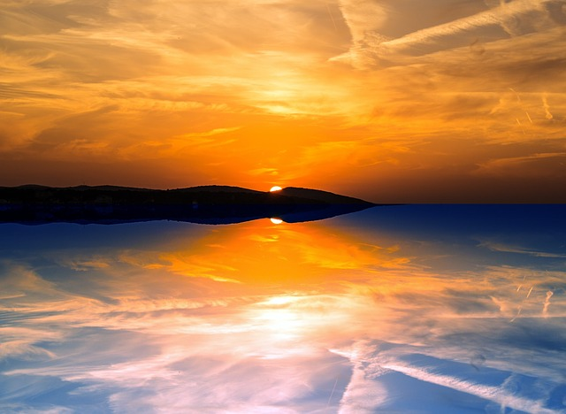 An image of a sunset at the shore, with the sun hidden by a spit of land, but bright colors are reflected in both sky and water.