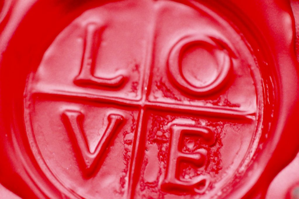 An image of a red wax seal with the word LOVE embossed in it.