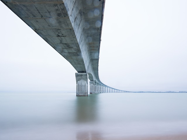 An image taken underneath a long bridge, showing the supports going into the water.