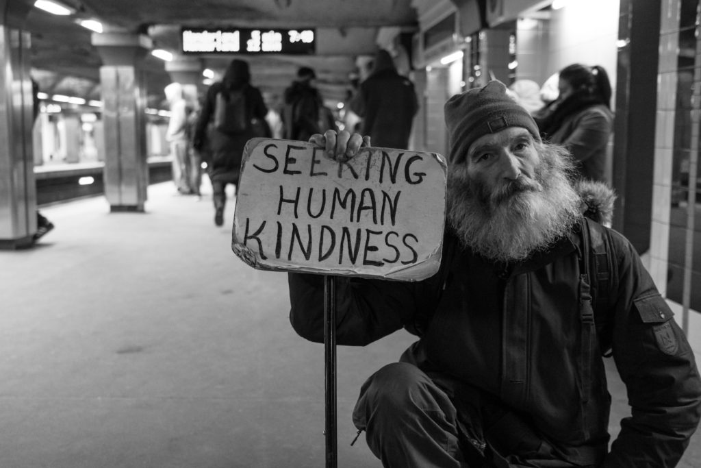 A photo of a shaggy, bearded man holding a sign that says, Seeking Human Kindness.