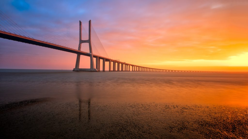 An image of a long bridge curving over low water, disappearing into a sunrise.