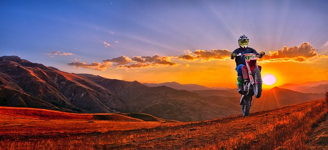An image of a motocross rider doing a wheelie with a sunset over a mountain range in the background.