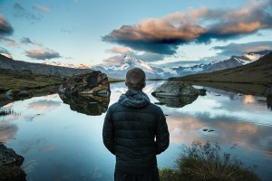A man viewing a serene lake and mountain scene
