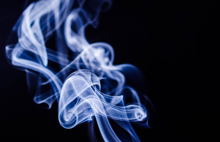 smoke curling against a dark background