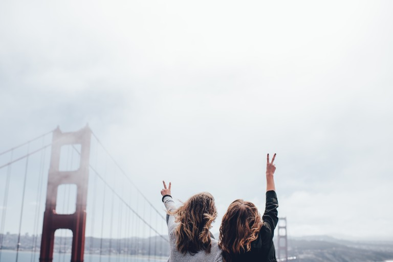 Two friends holding their fingers high in peace signs.