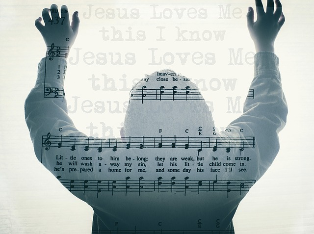 """a person with hands raised appears over the sheet music for """"Jesus Loves Me"""""""