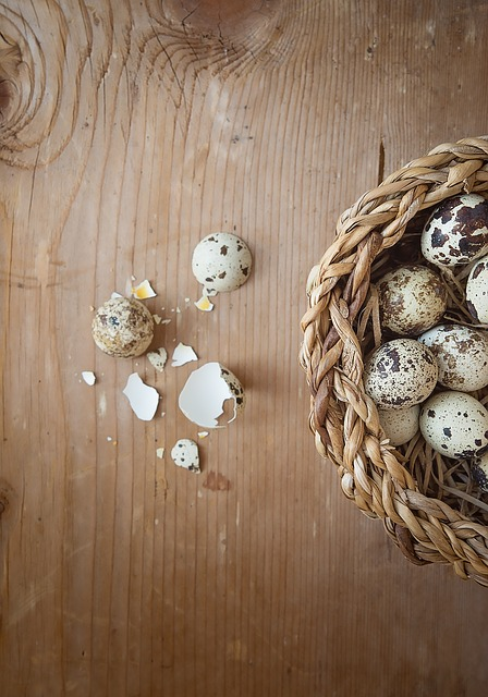 a basket of speckled eggs, with one broken on the table