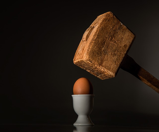 a heavy wooden mallet is poised above an egg