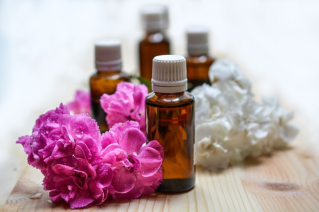some bottles of essential oils are nestled among some flowers