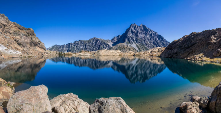 a mountain and blue sky are reflected in a lake