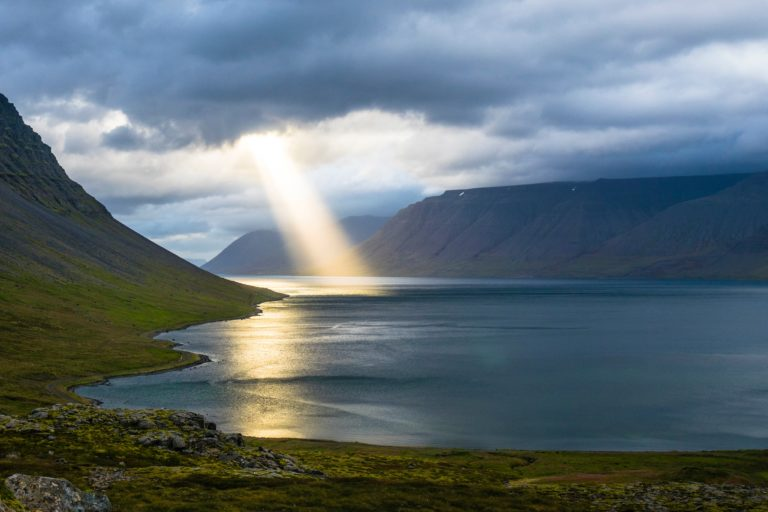 a stream of light shines down from heavy clouds