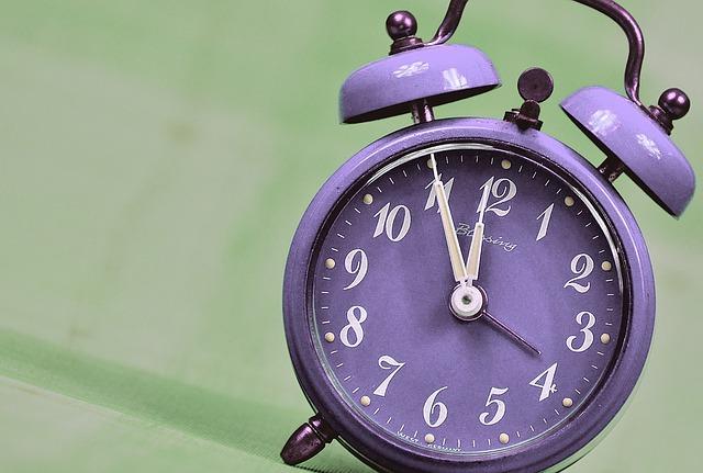 a purple alarm clock shows 11:55