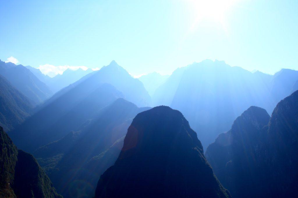 the sun shines behind a mountain peak