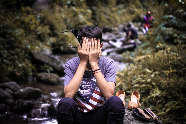 a man sits by a stream with his face in his hands