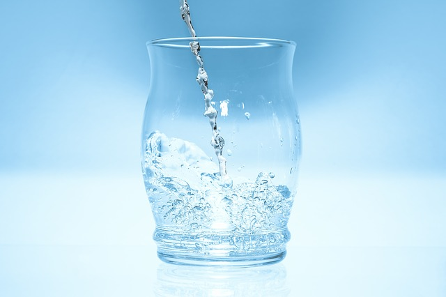 an image of a glass with water pouring in and splashing