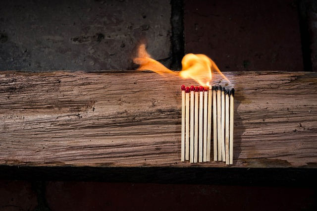 a small group of lit matches rests on a piece of wood