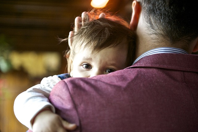 The image shows a father tenderly holding his young child.